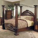 Beautiful wooden canopy bed design in luxurious dark brown bedroom