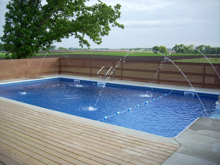 Backyard pool designs with fountain and wooden deck