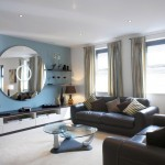 african living room decor in blue wall and black leather couches