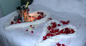 bedroom decoration for valentines day with hearts made from towels and rose petals