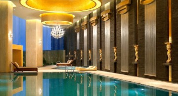 indoor swimming pool designs with low lights and grecian statuettes