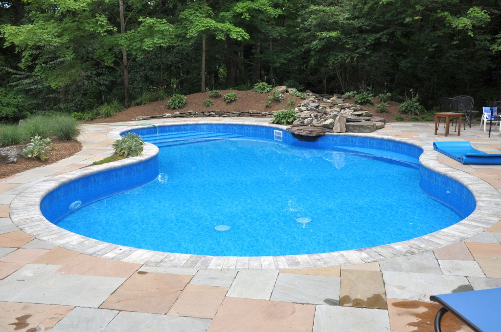 Kidney shaped swimming pools with stone deck for Kidney shaped above ground pool