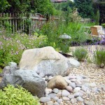 landscaping designs with big rocks and white fences