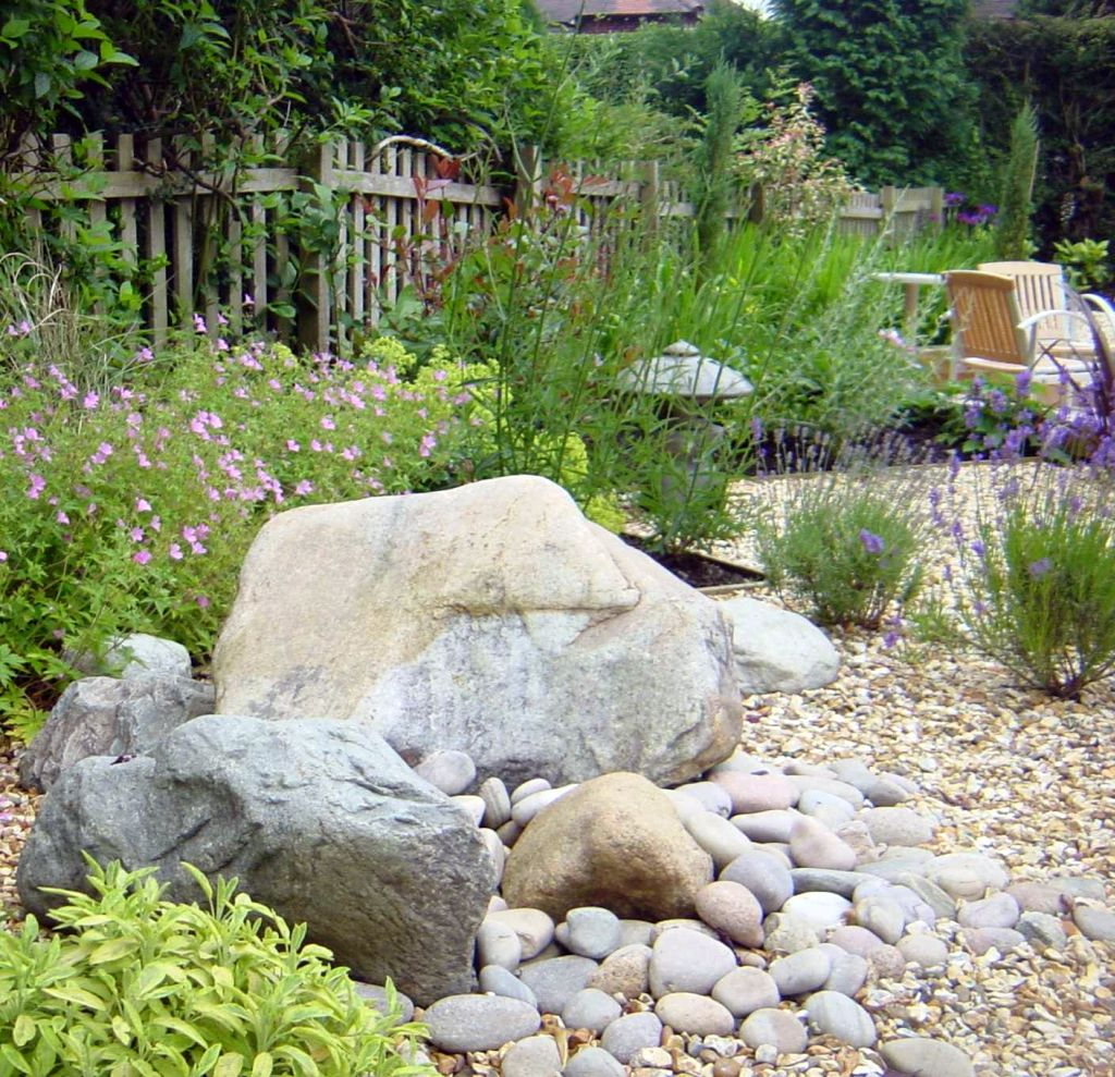 Landscaping designs with big rocks and white fences for Large white landscaping rocks