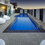 lap pool designs with stone deck and contemporary furnitures
