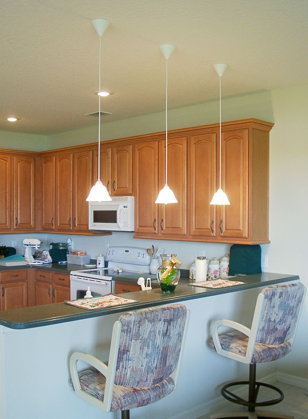 Low hanging mini pendant lights over kitchen island for an for Kitchen pendant lighting island