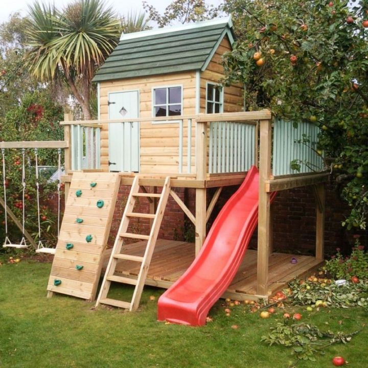 luxury outdoor playhouse with red slide and swings