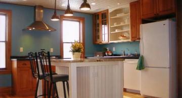 white kitchen island with sink in blue walled kitchen