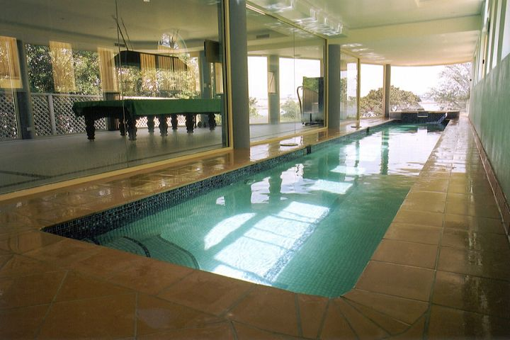 indoor lap pool with glass door and pool table