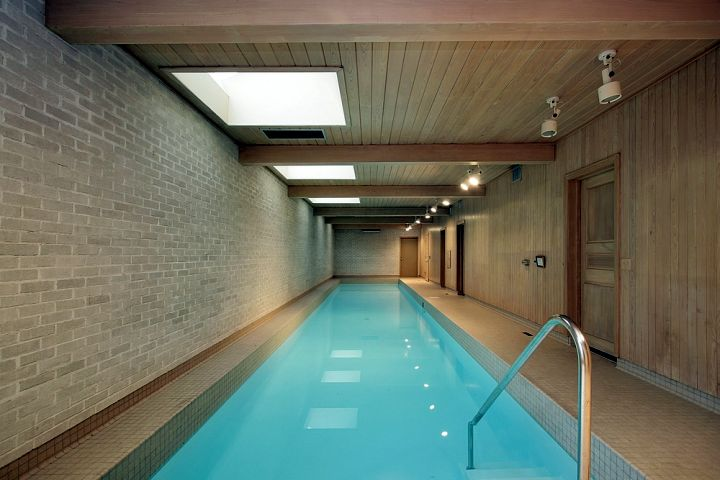 minimalist indoor lap pool with brick walls and wooden ceiling