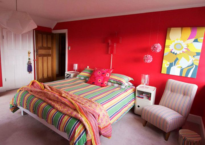 red bedroom walls with colorful bedding