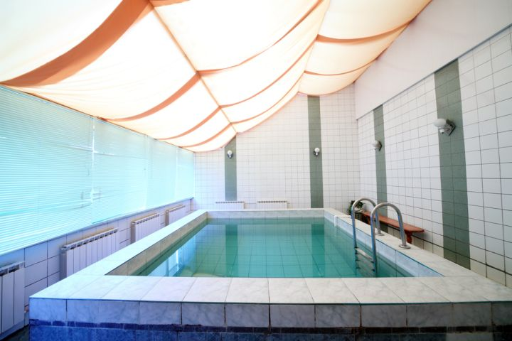 small enclosed swimming pool with unique ceiling