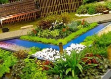 featured of terraced flower garden with small pond and garden chair