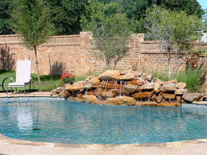 Natural red stone pool waterfall ideas for Pool design rochester ny