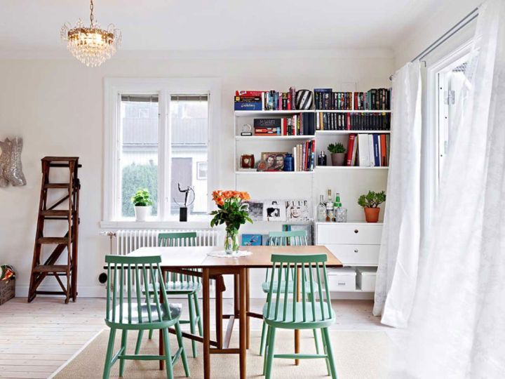 bookshelves in dining room in white and cerulean dining chairs