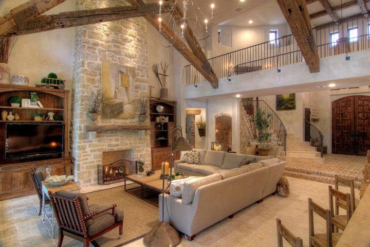 tuscan living room designs with criss crossed beams and stone fireplace