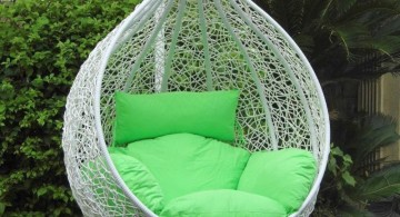 bedroom swing chair in white wicker and green cushions