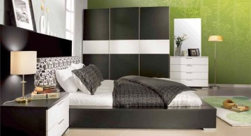 modern mens bedroom with green accent wall and black closet