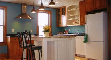 white kitchen island with sink in blue walled kitchen