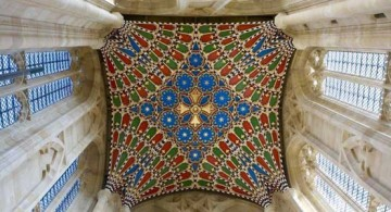 A very high vaulted ceiling design painted in red, blue, and green
