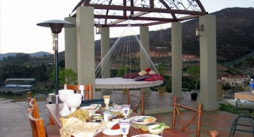 Outdoor swinging beds next to dining table