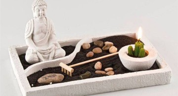 zen style mini japanese garden with black sand and Buddha statue